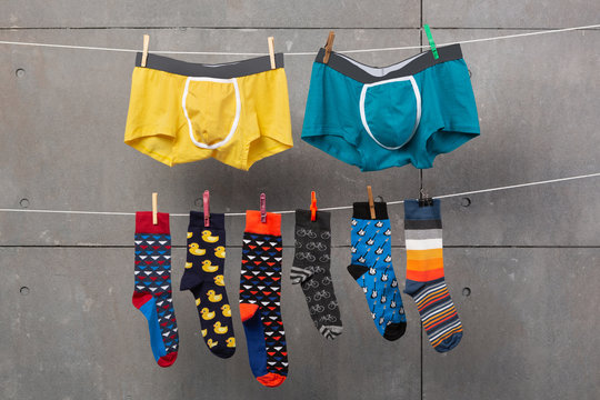 two men's shorts and many colored socks are hanging on the ropes, as if drying after washing, concept, on a gray background