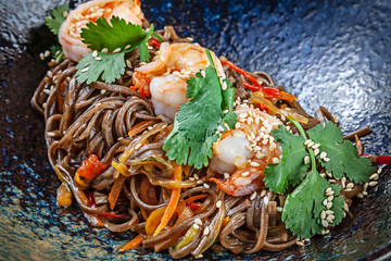 Close up on buckwheat noodles with shrimps served in black textured bowl. Thai cuisine. Seafood. Reaydy for eat. Picture for recipe. Copy space for design. Soba seafood