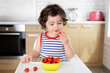 Young boy in high chair eating strawberries