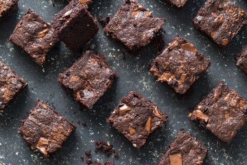 Chocolate brownie squares on black mottled background - baked chocolate brownies