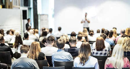 Wall Mural - Audience at the conference hall. Male speaker giving a talk in conference hall at business event. Business and Entrepreneurship concept. Focus on unrecognizable people in audience.