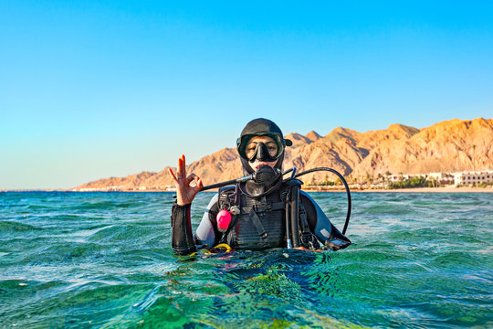 Woman diver floated on the surface of the sea and shows a hand sign that all is well.