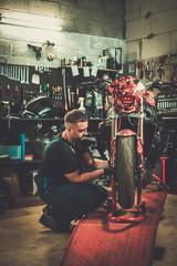 Mechanic arepairing a motorcycle in a workshop