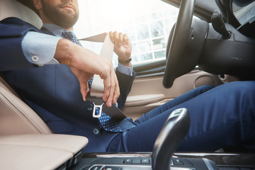 Safe driving. Cropped image of young businessman in formal wear is fastening the seat belt while sitting in his car