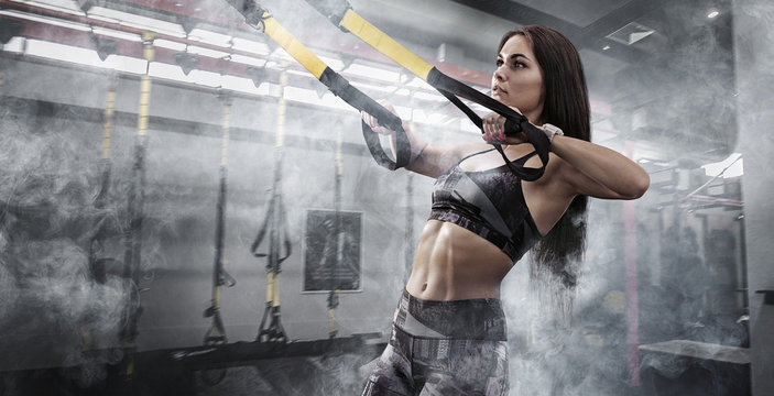 Sport backgrounds. Powerful attractive muscular woman fitness trainer do battle workout with ropes at the gym.