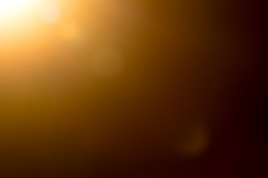 Lens flare and light beam on dark background yellow color, photo from lens camera
