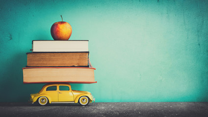 Education and creative teaching. Toy car, books and apple. Car is deshaped being brandless