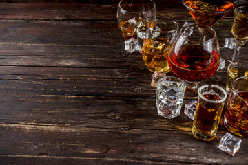 Assortment various hard and strong alcoholic drinks in different glasses: vodka, cognac, tequila, brandy and whiskey, grappa, liqueur, vermouth, tincture, rum, etc. Wooden background copy space Fototapete