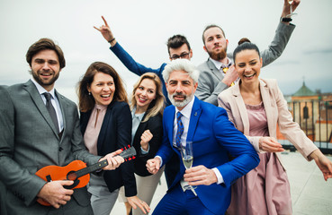 A group of joyful businesspeople having a party outdoors on roof terrace in city. Wall mural