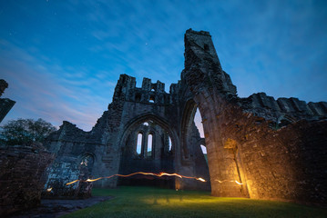 Starry night sky over ruins of light painted Llanthony Priory, Wales, UK