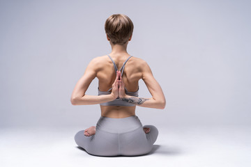 Young attractive Woman practicing home yoga, working out, wearing sportswear. Healthy life, keep fit concepts.