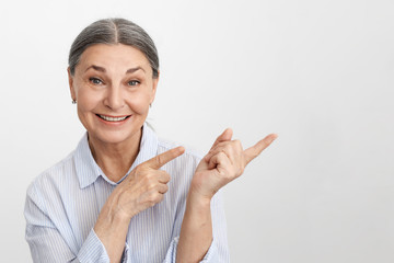 Isolated studio image of charismatic excited elderly female Human Resources expert with gray hair pointing index fingers to the right and smiling broadly, friendly showing you way to success