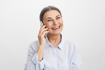 Studio shot of cheerful ecstatic senior elderly woman wearing elegant blue shirt laughing at good funny joke, showing her perfect straight teeth, enjoying nice phone conversation using mobile