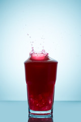 Splash on a glass of  raspberry juice representing the concept of without spilling a drop