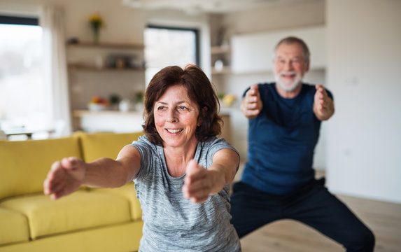 A senior couple indoors at home, doing exercise indoors.