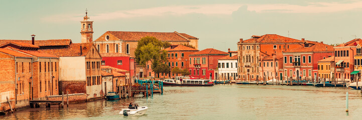 Venice Italy - May 25, 2019: View on Murano island with the central canal, bridge, boats, shops and tourists during sunset