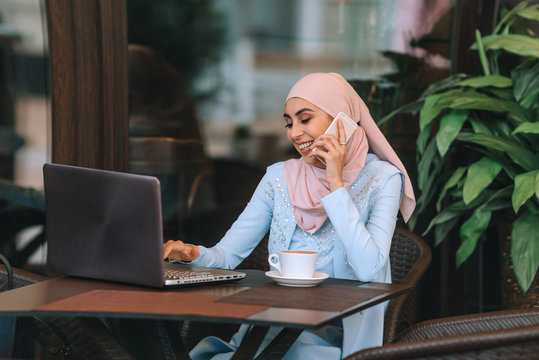 Muslim business woman working on a laptop in a cafe with a cup of coffee and chewing.
