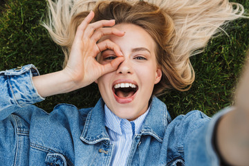 Photo of young kind woman taking selfie photo and showing ok sing while lying green grass in park