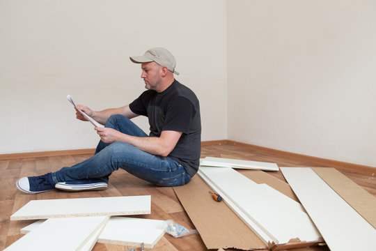 Man reading assembly instructions for furniture in new house. Carpenter repair and assembling furniture at home