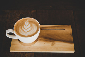 Cup of coffee latte on wood table in coffee shop cafe