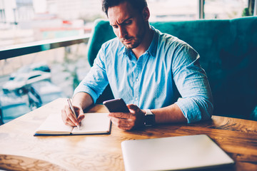 Concentrated handsome man dressed in stylish blue shirt looking at modern telephone and rewriting...