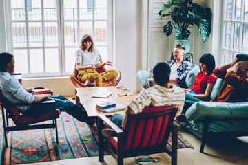 Multicultural group of positive young people having fun during friendly meeting on weekend in modern apartment with design interior.Cheerful diverse hipster guys resting in comfortable hostel