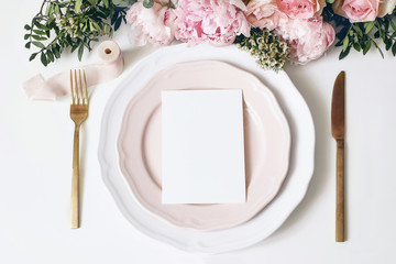Feminine wedding, birthday desktop mock-up scene. Porcelain plates, blank paper greeting, menu card, ribbon, golden cutlery, leaves,roses, peony flowers. White table background. Flat lay, top view