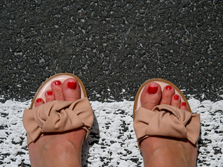 op view photo of woman feet in sandals on the pedestrian crossing