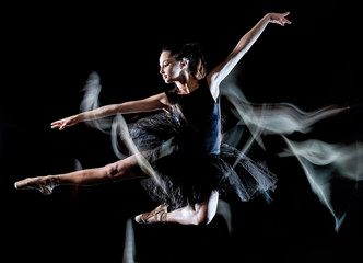 one caucasian young woman ballerina dancer dancing isolated on black background with  light...