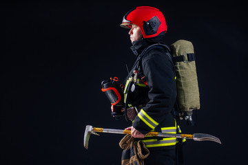 portrait strong fireman in fireproof uniform holding an ax in his hands black background studio