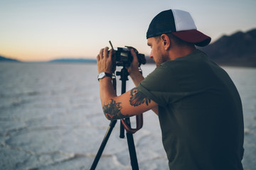 Skilled male travel blogger shooting film about natural landscape of Badwater basin work during expedition, tourist photographer taking pictures of scenic sunset in Death Valley during summer journey