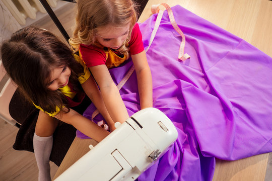 two cute little sisters playing with sewing machine workshop manikin