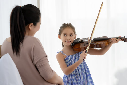 The daughter is playing violin for her mother to listen.