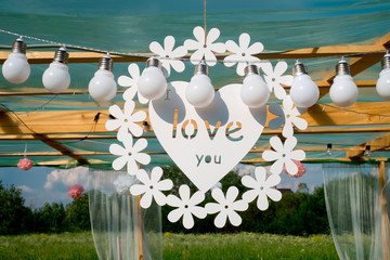 Love word and white hearts on paper background. Valentines Day concept photo. chamomile. white light bulbs