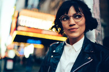 Pretty stylish hipster girl with short haircut looking away walking in New York street with neon lights.Cute fashionable young woman in cool eyewear enjoying nightlife in downtown of metropolis