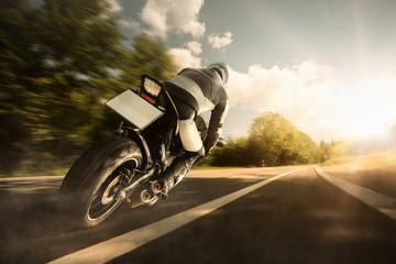 Motorradfahrer fährt auf Landstraße dem Sonnenuntergang entgegen