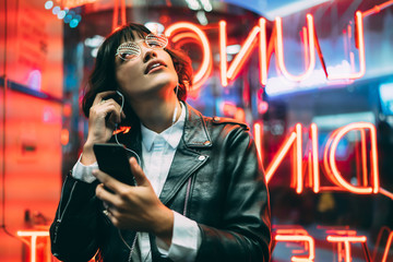 Excited female lover of music dressed in stylish leather jacket listening songs online in earphones connected to smartphone while enjoying night lights and neon illumination in New York City Wall mural