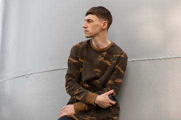 Nice serious young man in a stylish green military shirt c fashionable hairstyle rests near the metal gray wall on a sunny summer day. Handsome guy model outdoors. Trendy menswear.