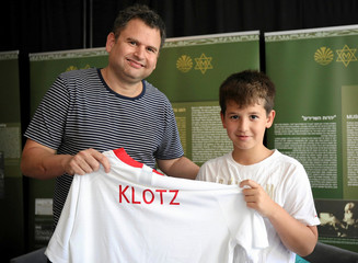 Yoav Dekel and his son, relatives of former football player Jozef Klotz, hold a football shirt during an event to remember Polish Jewish footbal legends in Warsaw