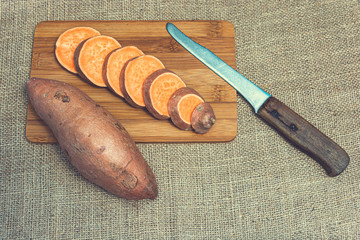 Sliced raw sweet potatoes on a wooden cutting board and jute backgroud. Product photo of batats. Healthy diet for vegetarians and vegans. Source of vitamins. Wooden plank with batatas and knife