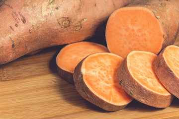 Sliced raw sweet potatoes on a wooden cutting board. Product photo of batats. Healthy diet for vegetarians and vegans. Source of vitamins.