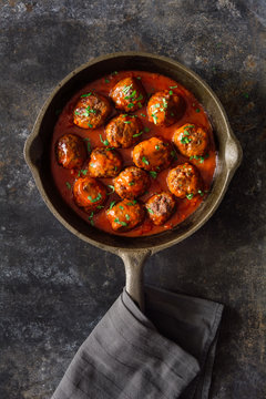 Simple beef meatballs with tomato sauce in cast iron skillet. Natural light.