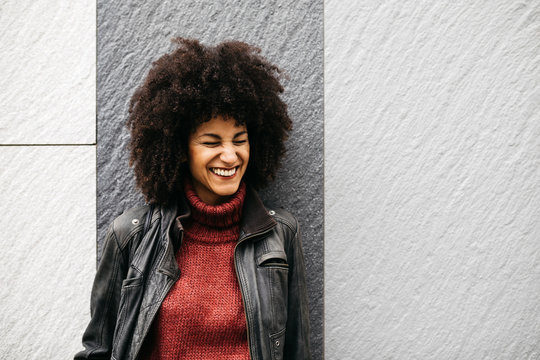 Stylish woman in leather jacket smiling with eyes squinted over