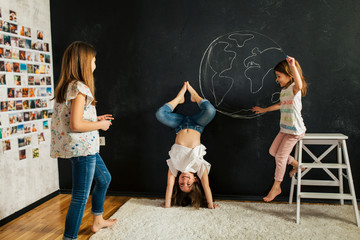 Young girls drawing planet earth on a blackboard and playing in the room