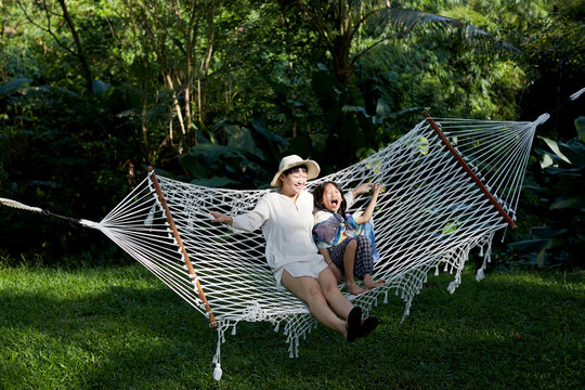 Asian Mother and daughter happy time sitting on hammock in nature woods