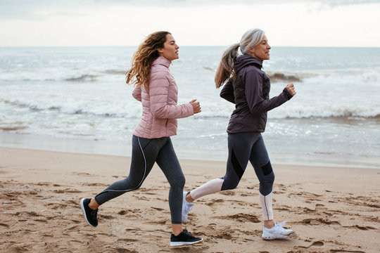 Senior woman and her daughter running on the beach.