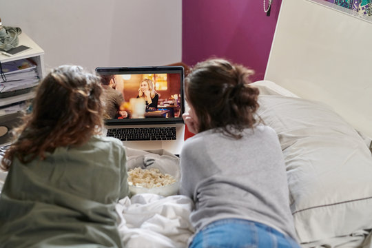 Women lounging on bed with laptop and popcorn