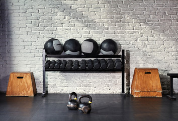 A sunlit empty gym with a rack of weights.