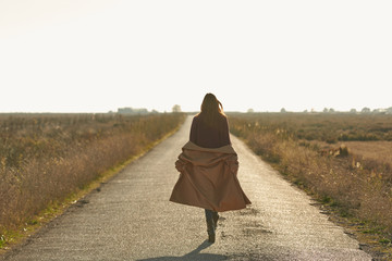 Woman with lowered coat walking on sunlit road in countryside.