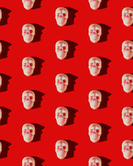 Pattern of white and red Halloween-themed skull candies on a red background